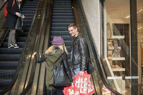 Young couple moving up escalator with shopping bags,  New York, USA Royalty-free stock photo