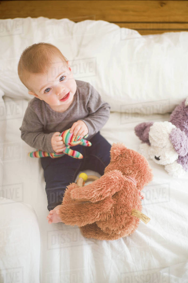 Baby Girl Sitting On Bed Holding Soft Toys Looking Up At Camera
