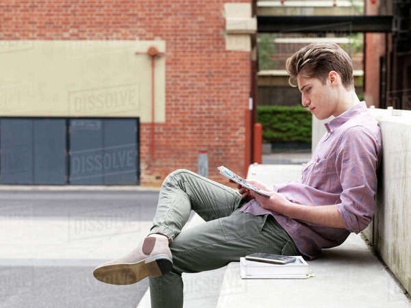 Young man sitting on step, outdoors, reading book Royalty-free stock photo