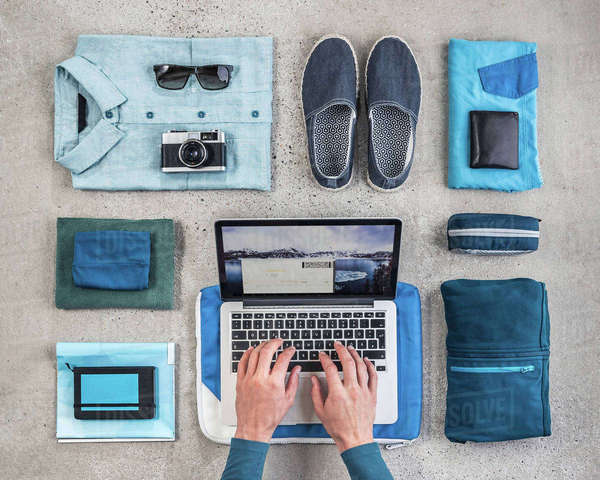 Overhead view of man's hands typing on laptop surrounded by travel packing items, with blue shirt,  retro camera, wash bag and notebook Royalty-free stock photo