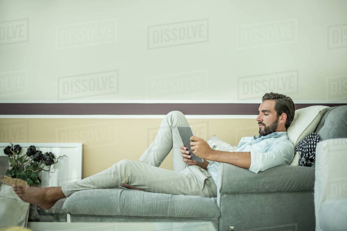 Young Man Reclining On Hotel Room Chaise Longue Using Digital D943 203 032