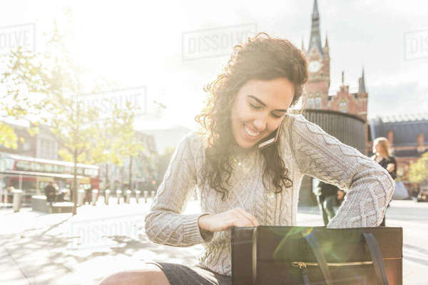 Mid adult woman, outdoors, sitting bench, looking in bag, using smartphone Royalty-free stock photo