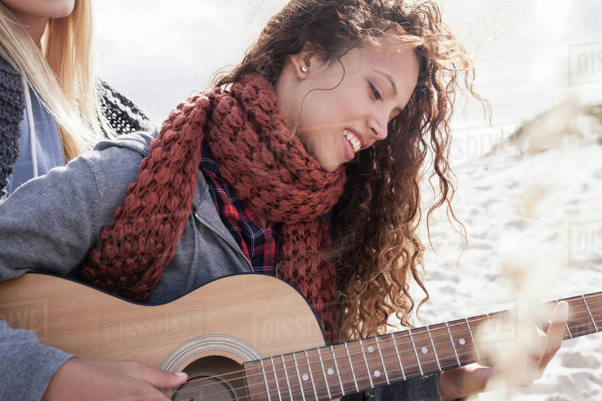 Two young female friends playing guitar at beach, Western Cape, South  Africa stock photo