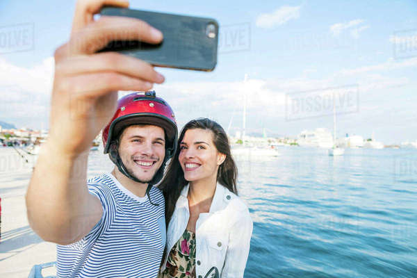 Young moped couple taking selfie on harbour, Split, Dalmatia, Croatia Royalty-free stock photo