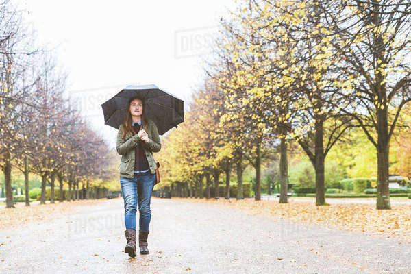 Young woman walking through park, carrying umbrella Royalty-free stock photo