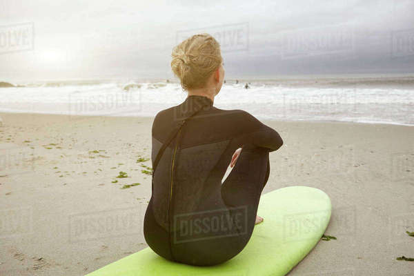 Female surfer sitting on surfboard looking out from Rockaway Beach, New York, USA Royalty-free stock photo