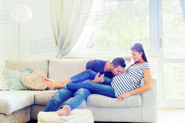 Man on sofa kissing pregnant woman's stomach Royalty-free stock photo