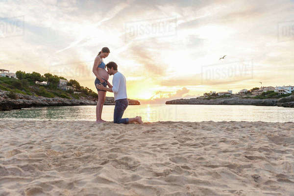 Pregnant woman and man on beach, man kissing woman's stomach Royalty-free stock photo