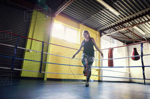 Young female boxer skipping in boxing ring Royalty-free stock photo