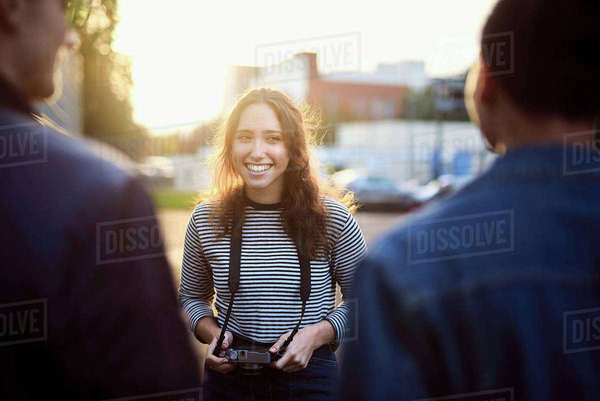Over shoulder view of young woman talking to male friends  on sunlit street Royalty-free stock photo