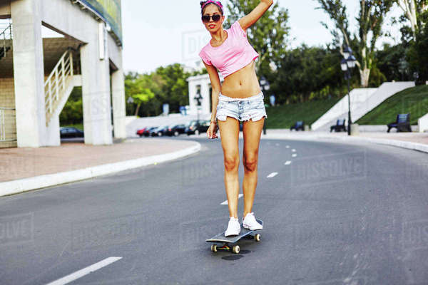 Young woman skateboarding along road Royalty-free stock photo