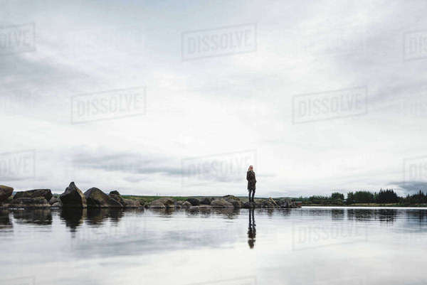 Woman on edge of water, Hafravatn, Iceland Royalty-free stock photo
