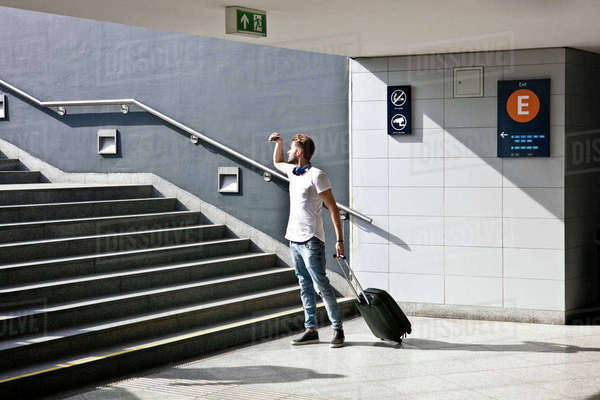 Young man with wheeled trolley bag, in front of steps in train station Royalty-free stock photo