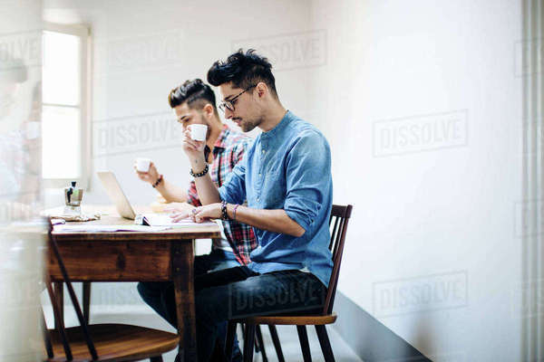 Male couple sitting at table, drinking coffee, using laptop Royalty-free stock photo