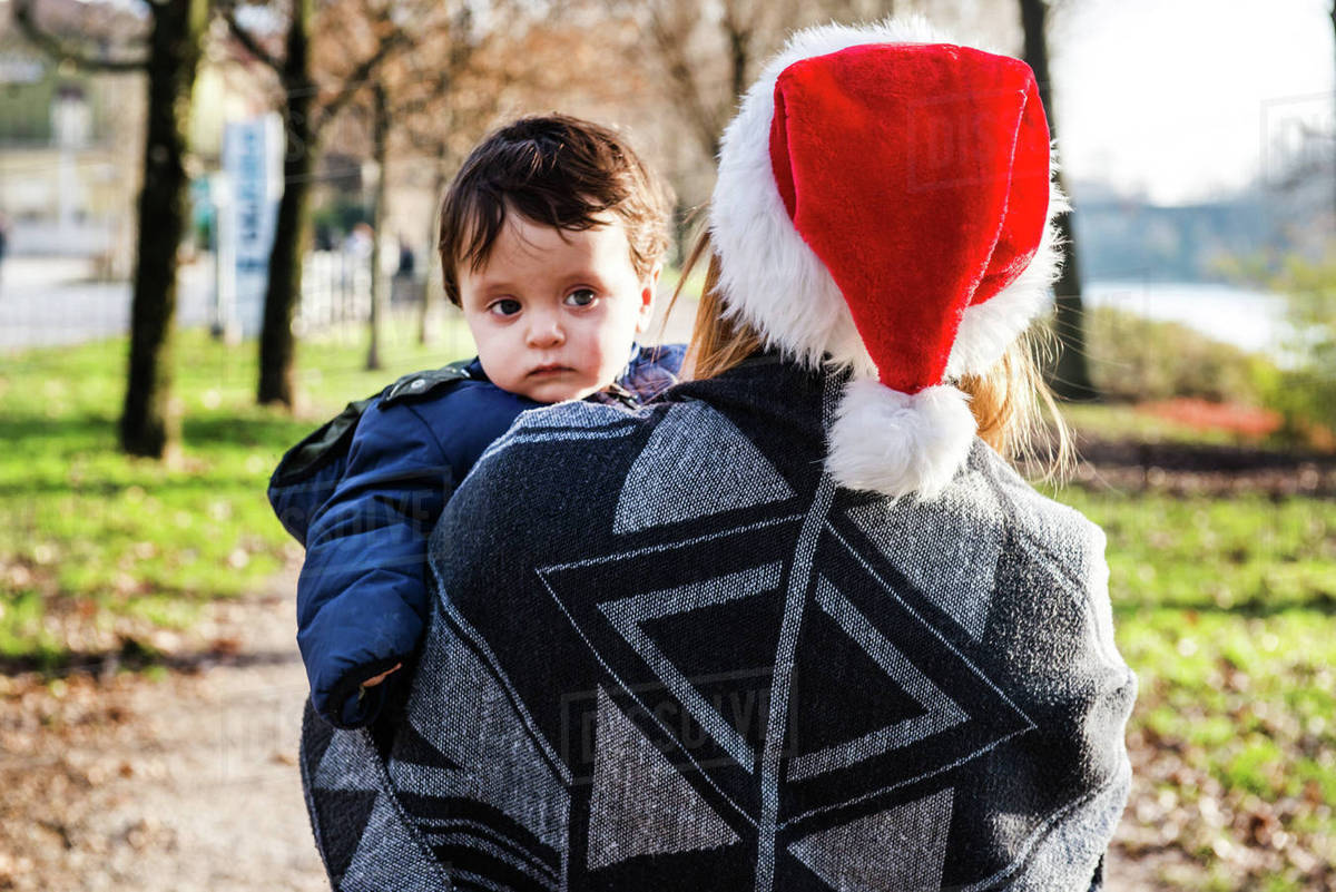 36c6514a503e Over shoulder view of young woman in santa hat carrying baby boy in ...