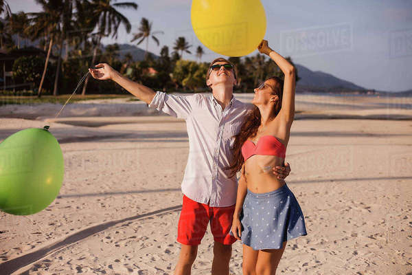 Young couple on beach looking up at balloons, Koh Samui, Thailand Royalty-free stock photo