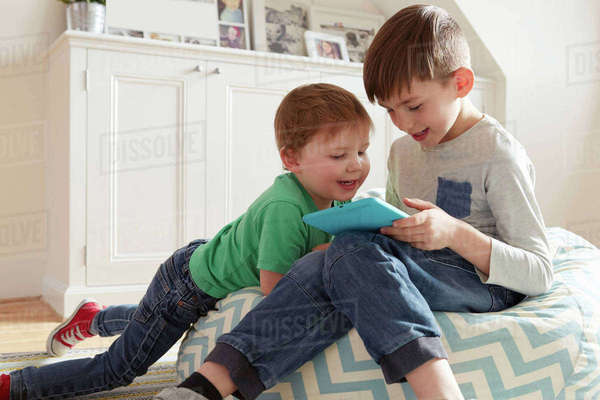 Male toddler and brother on beanbag chair looking at digital tablet Royalty-free stock photo