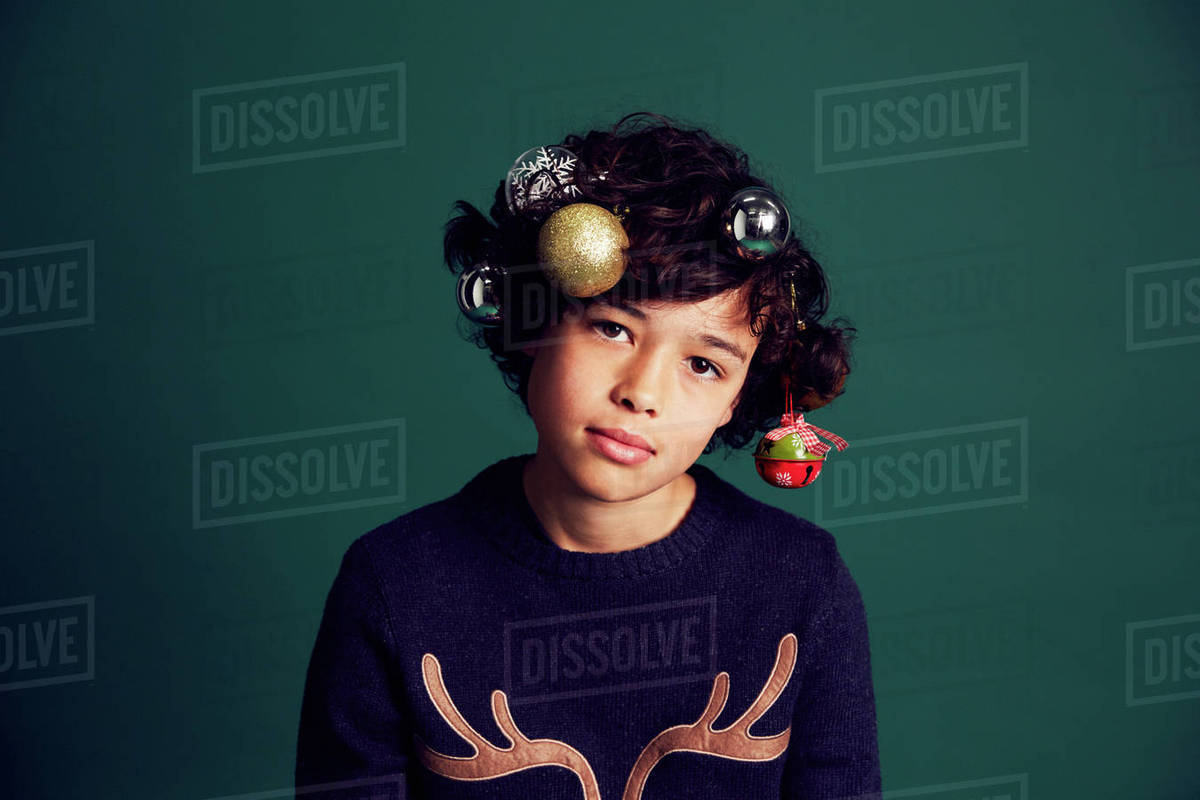 72208ac5eee Portrait of teenage boy wearing Christmas jumper, and baubles in hair stock  photo