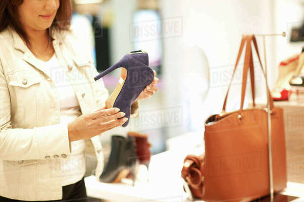 Mid section of woman holding high heeled shoe in shop, Dubai, United Arab Emirates Royalty-free stock photo