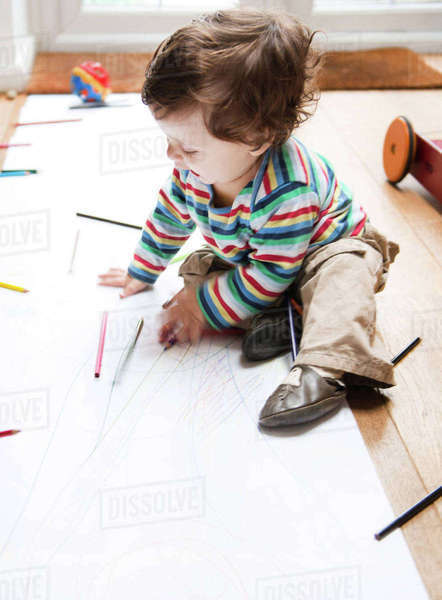 Male toddler sitting on floor drawing on long paper Royalty-free stock photo