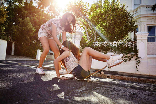 Teenage girl catching friend falling off skateboard, Cape Town, South Africa Royalty-free stock photo