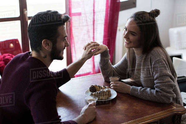 Couple sitting at table holding hands, drinking coffee Royalty-free stock photo