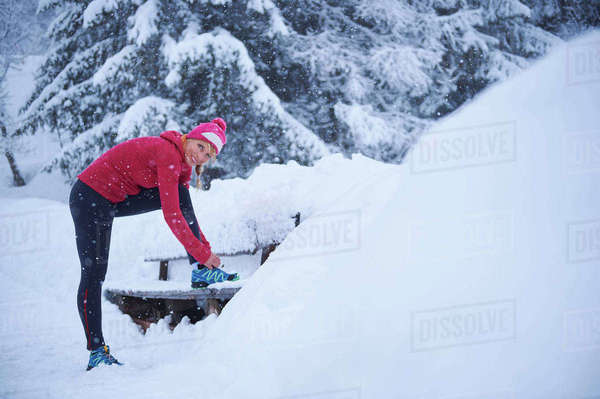 Portrait of female runner tying trainer laces on park bench in deep snow, Gstaad, Switzerland Royalty-free stock photo