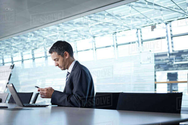 Businessman looking at smartphone at boardroom table Royalty-free stock photo