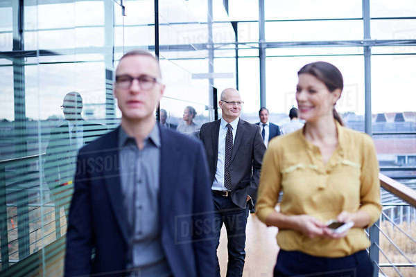 Businessmen and woman walking and talking on office balcony Royalty-free stock photo