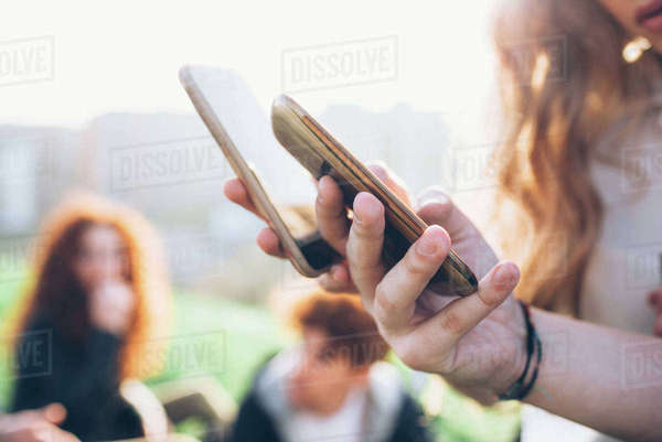 Two young women outdoors, looking at smartphones, mid section, close-up Royalty-free stock photo
