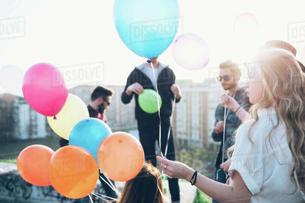 Group of friends enjoying roof party, young woman holding helium balloons Royalty-free stock photo
