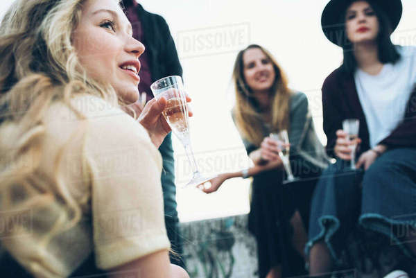 Group of friends outdoors, holding champagne glasses, low angle view Royalty-free stock photo