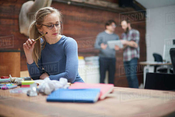 Female designer contemplating at design studio desk Royalty-free stock photo