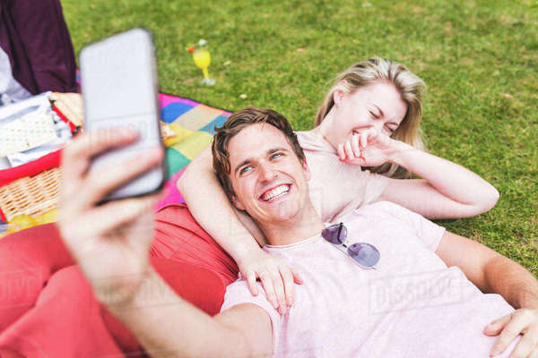 Group of friends relaxing on picnic blanket, in park, man taking selfie using smartphone Royalty-free stock photo