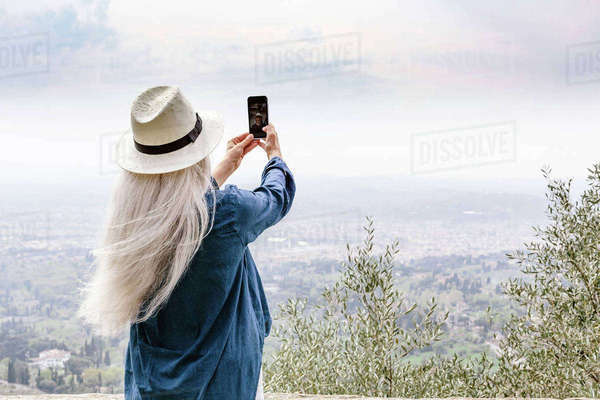 Rear view of mature woman with long grey hair photographing view, Fiesole, Tuscany, Italy Royalty-free stock photo