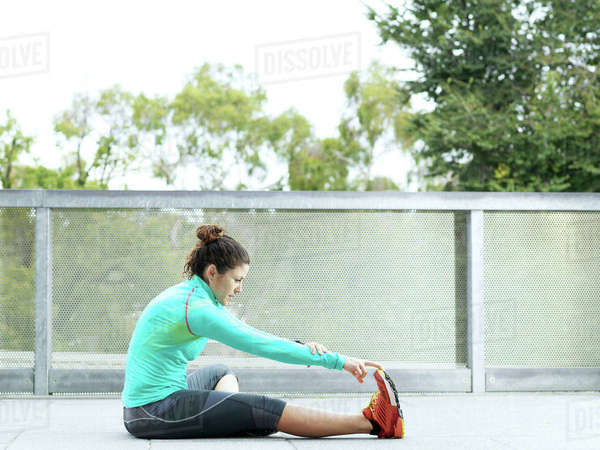 Mature female ultra runner sitting on urban footbridge touching toes Royalty-free stock photo