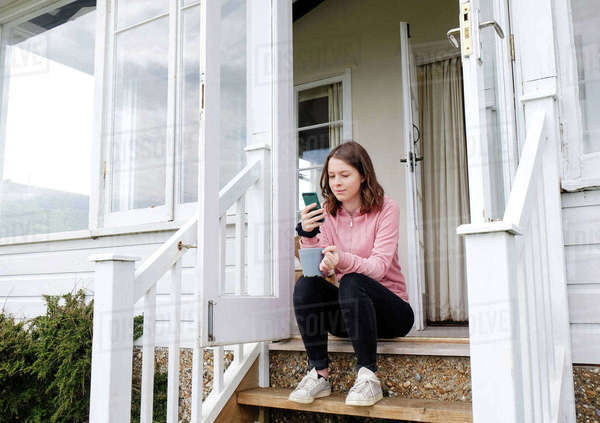 Young woman sitting on porch stairs with coffee cup looking at smartphone Royalty-free stock photo