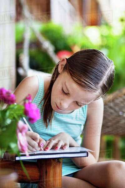 Girl writing on notebook outdoors Royalty-free stock photo