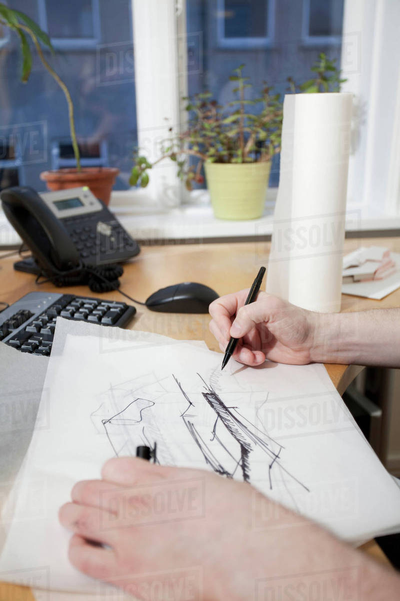architect sketching at desk stock photo dissolve