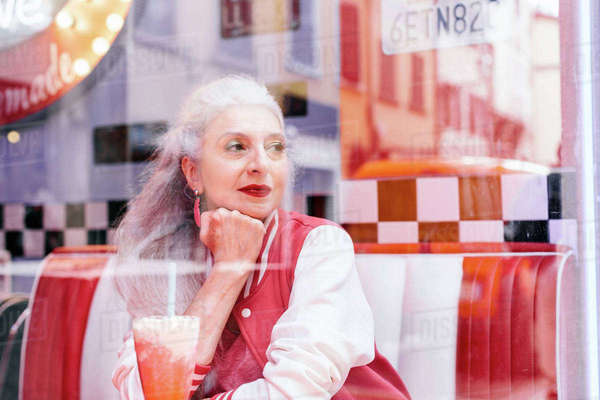 Mature woman in baseball jacket looking through window from 1950's diner Royalty-free stock photo