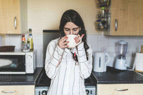 Young woman at home, in kitchen, wearing pyjamas, drinking cup of coffee Royalty-free stock photo