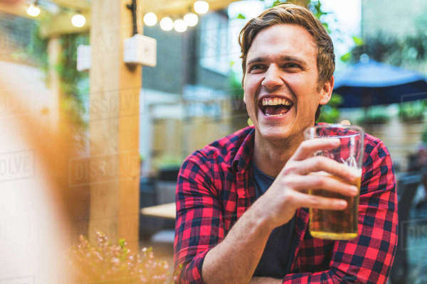 Couple sitting in pub garden, holding pint of beer, laughing Royalty-free stock photo