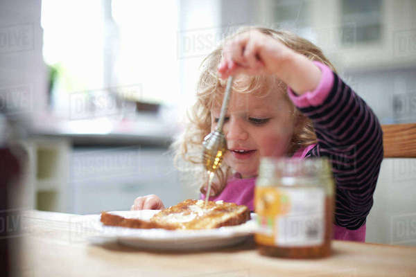 Young girl sitting at kitchen table, drizzling honey on toast Royalty-free stock photo