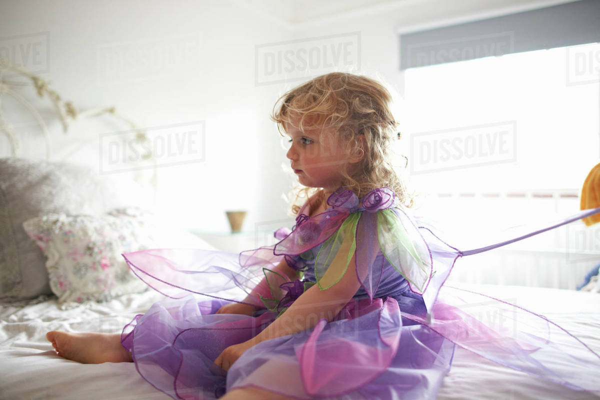 Young girl dressed in fairy costume, sitting on bed Royalty-free stock photo