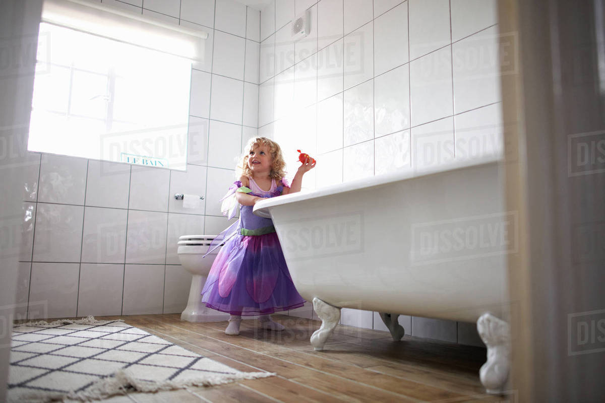 Young girl dressed in fairy costume, standing beside bathtub Royalty-free stock photo