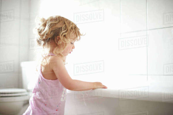 Young girl standing beside bathtub Royalty-free stock photo