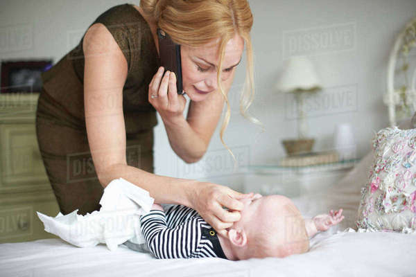 Mother changing baby son's nappy while using mobile phone Royalty-free stock photo