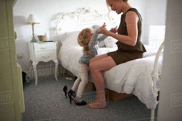Mother holding daughter balancing in high heel shoes Royalty-free stock photo