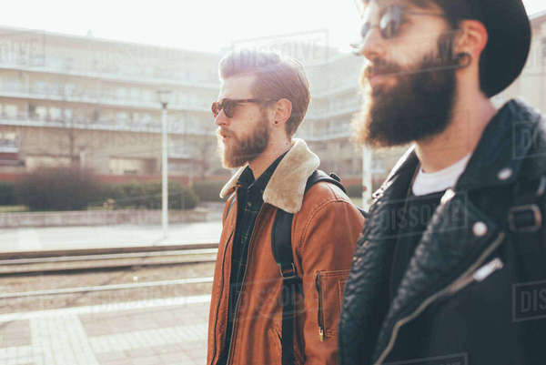 Side view of two young male hipster friends wearing sunglasses in city housing estate Royalty-free stock photo