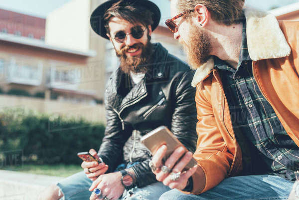 Two young male hipsters sitting on wall with smartphones Royalty-free stock photo